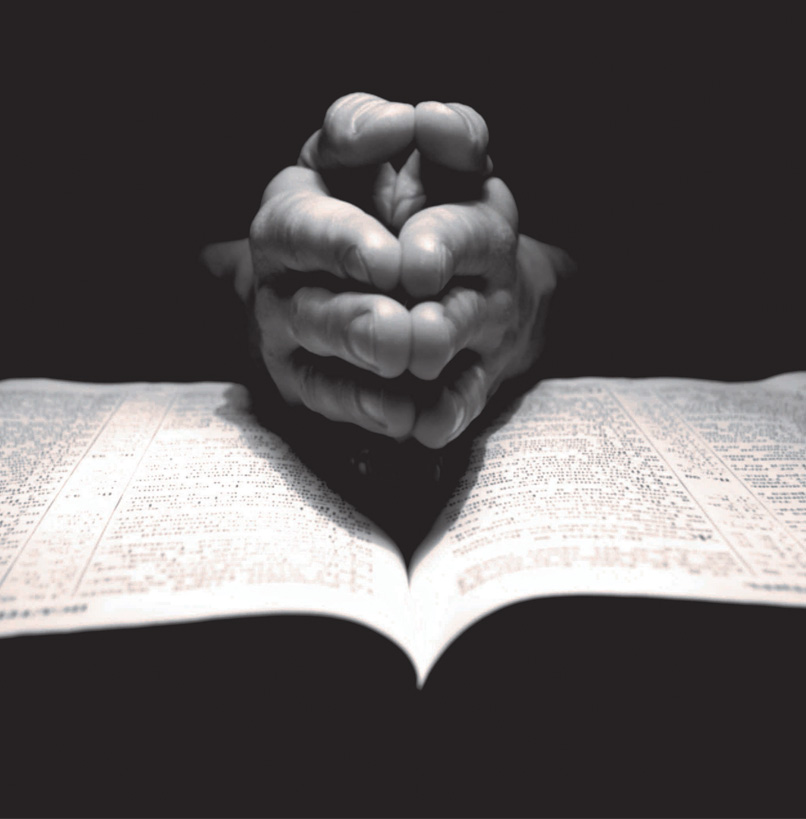 A pair of hands folded together over a bible in an act of prayer.