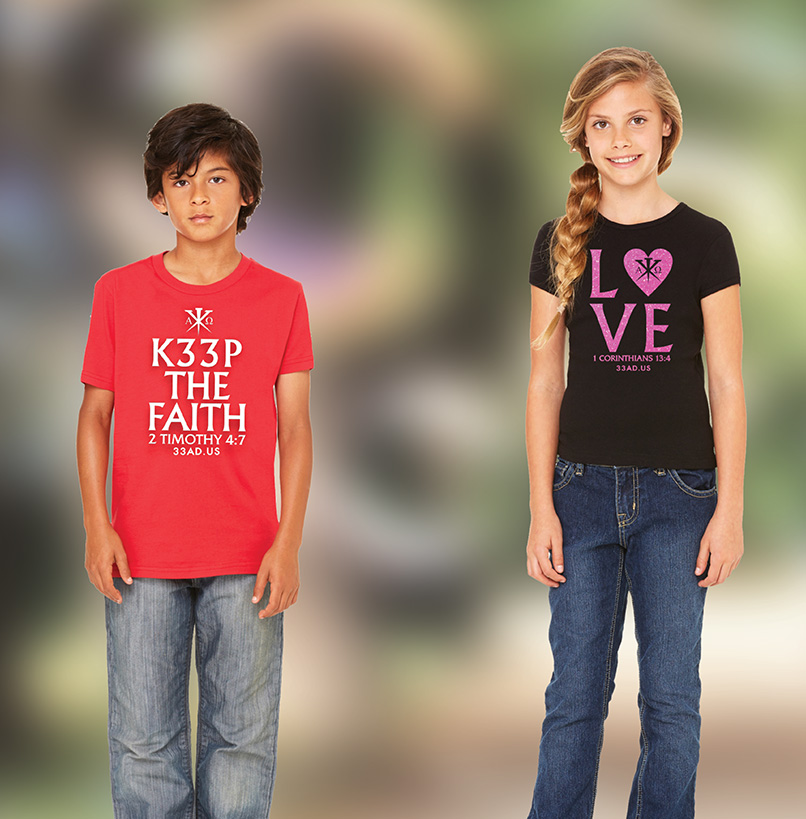 A young boy and young girl standing in front of a blurred multi-color backdrop, each wearing a 33 Anno Domini shirt, the boy's red with a white embellishment, the girl's black with a glittery red embellishment.