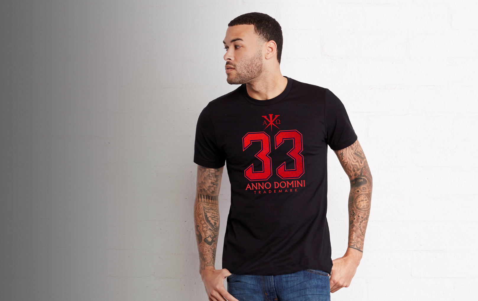 A heavily tattooed man standing on a gray and white backdrop, wearing a black 33 Anno Domini shirt with red embellishment.